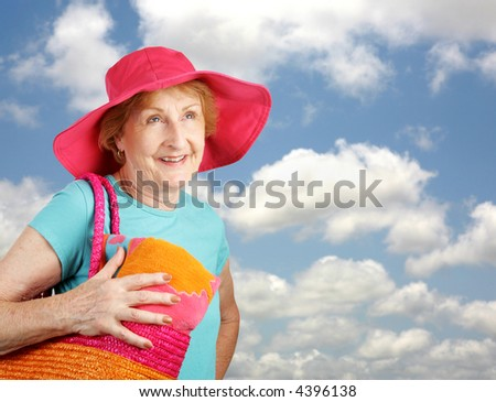 A pretty senior woman headed to the beach on a beautiful sunny day.