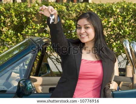 A pretty, smiling, young woman standing in front of a sports car holding out a set of car keys. - stock photo