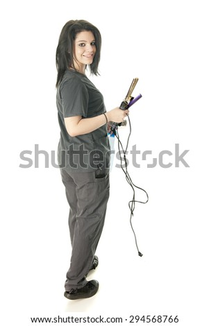 A pretty student of cosmetology looking back as she carries her spray bottle, curling iron and comb.  On a white background. - stock photo