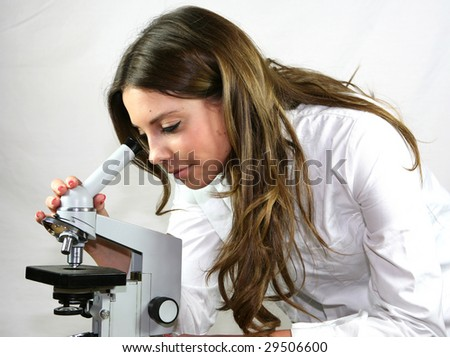 A pretty technician looks down a microscope in a hospital laboratory