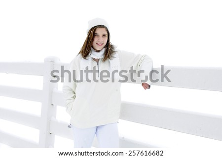 A pretty teen brunette outside while snowing.  She's dressed totally in white standing by a show-covered white fence. - stock photo