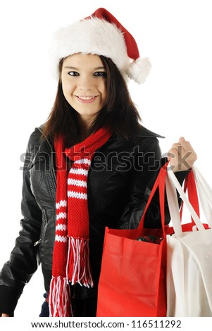 A pretty teen girl happily wearing a Santa hat and red scarf while carrying cloth shopping bags.  On a white background.