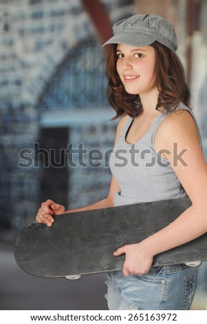 A pretty teen girl looking at the viewer as she carries her skateboard past buildings.   - stock photo