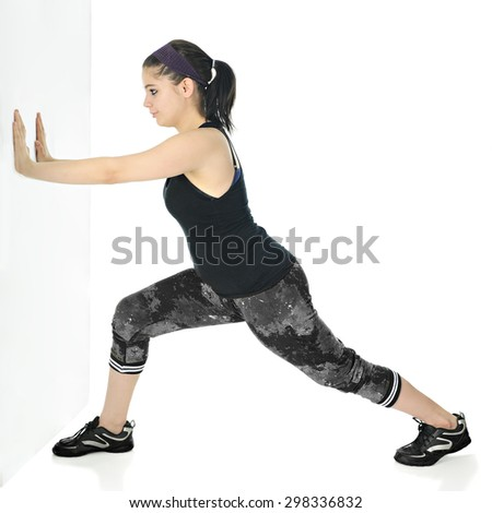 A pretty teen girl stretching her calves as she pushes against a wall and leans forward in a black and gray work outfit.  On a white background. - stock photo