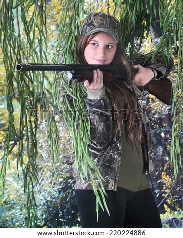 A pretty teen hunter preparing to aim her rifle.   - stock photo