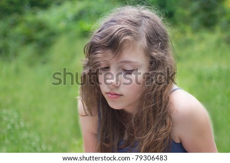 A pretty teenage girl sitting against green grass looking bashfully away - stock photo
