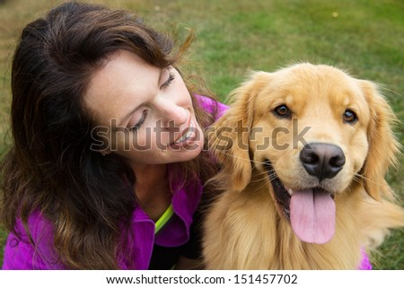 A pretty woman and her golden retriever dog - stock photo