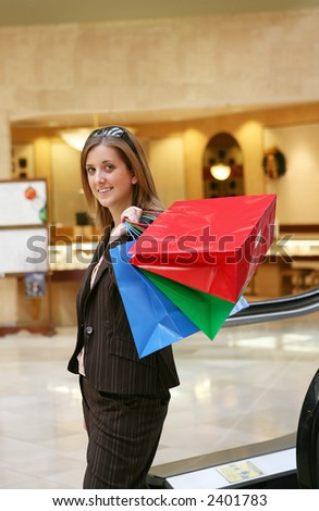 A pretty woman coming down the escalator with shopping bags in hand - stock photo