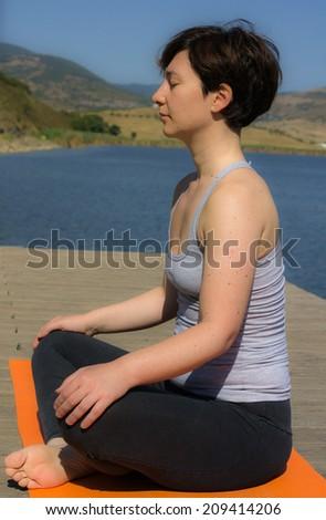 a pretty woman doing yoga at the lake - stock photo