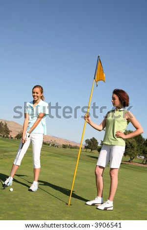 A pretty woman golfer ready to putt the ball into the hole - stock photo