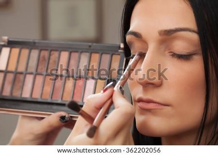A pretty woman having makeup applied by a makeup artist - stock photo