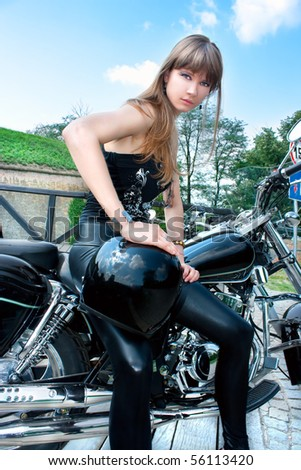 A pretty woman hold a black motorcycle helmet and posing