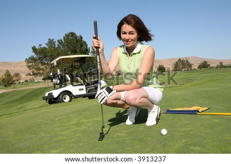 A pretty woman in the middle of a golf game - stock photo