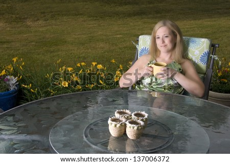 A pretty woman on a patio with coffee - stock photo