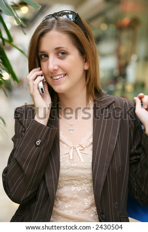 A pretty woman on the phone inside a mall - stock photo