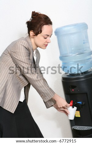 A pretty woman taking a water break in the office - stock photo