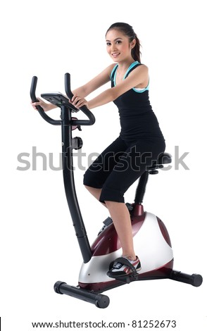 A pretty woman training on exercise bike - stock photo