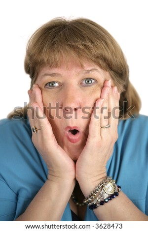 A pretty woman with her hands on her face wearing a very shocked expression.  White background - stock photo