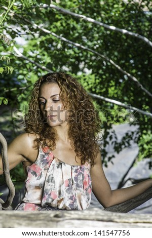 A pretty woman with long brown curly hair is thinking in a wood area./Thinking Outside - stock photo