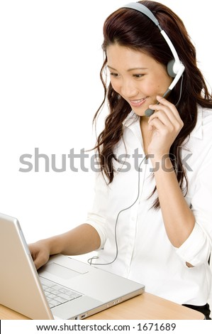 A pretty young asian woman working on a helpdesk - stock photo