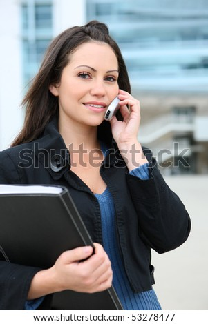 A pretty young business woman on mobile phone at office building - stock photo