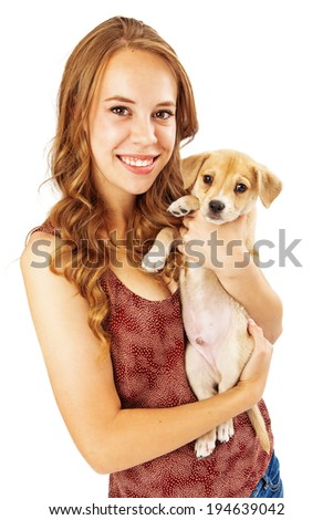 A pretty young female adult holding a mixed golden breed puppy and looking at the camera - stock photo