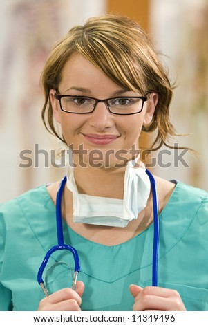 A pretty young female doctor in scrubs with a stethoscope