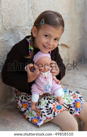 A pretty young girl cuddles and plays with her doll
