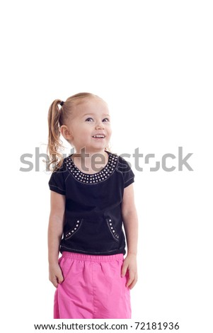 A pretty young girl looking up at something.  The photograph is isolated.  The child is wearing a black shirt and pink pants. - stock photo
