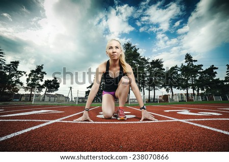 A pretty young girl running and stretching on the runway - stock photo