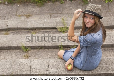 A pretty young girl sitting on the steps in the city Park. - stock photo