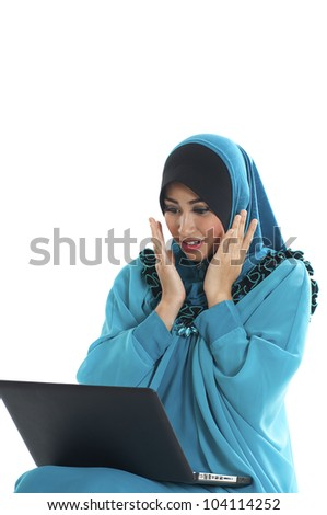 A pretty young Muslim women surprised in action while looking a laptop. Isolated on white background. - stock photo