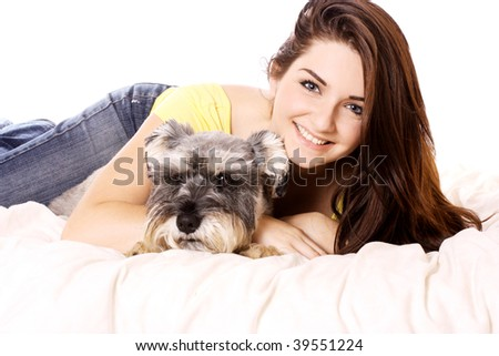 A pretty young smiling woman in bed with her Miniature Schnauzer.