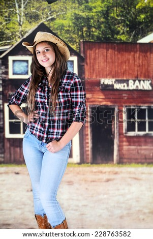 A pretty young teen happily standing in the main street of an old western town. - stock photo