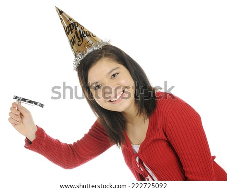 A pretty young teen in a party hat celebrating the New Year.  She's twirling a noisemaker.  On a white background. - stock photo