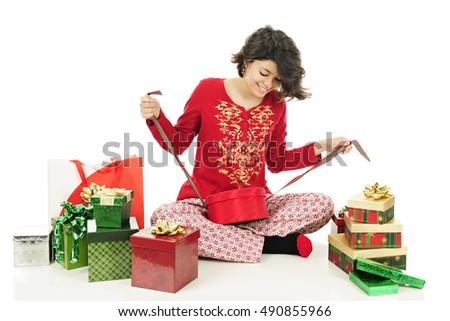 A pretty young teen in her pajamas happily tying up pre-decorated gift boxes with ribbons and bows.  On a white background.