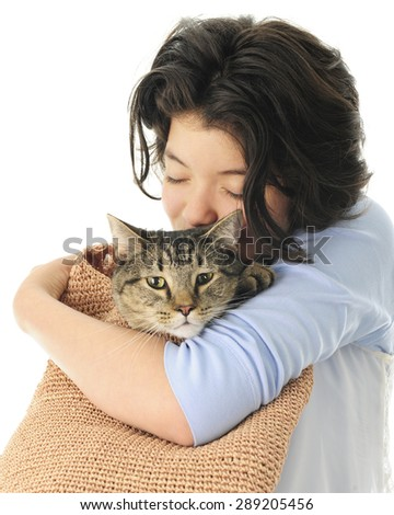 A pretty young teen snuggling (eyes closed) with her pet in a woven shoulder bag.  On a white background. - stock photo