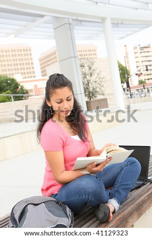 A pretty young teenage girl reading a book outside school building - stock photo