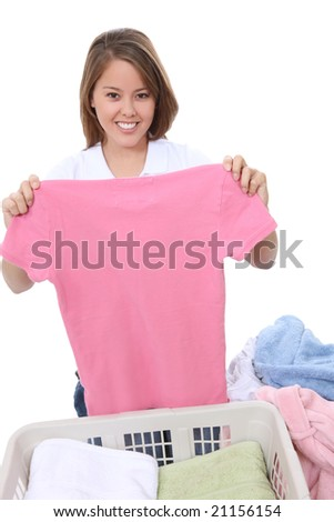A pretty young woman folding clothes at home - stock photo