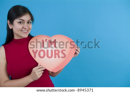 A pretty young woman holding a large valentine taken on a blue background with copy space. - stock photo