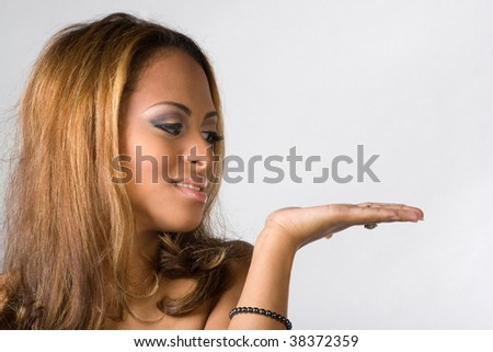 A pretty young woman holding her hand out with plenty of copy space.  Place your own object or text on her hand. - stock photo