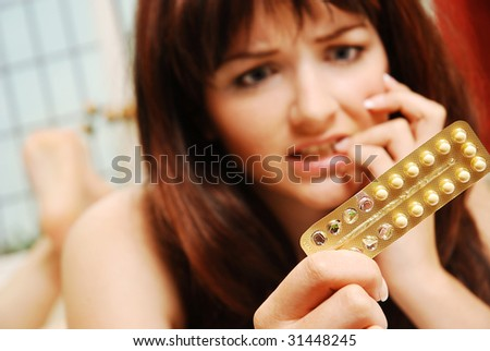 A pretty young woman looking at her contraceptive pills and pulling a worried face and biting her nails. - stock photo