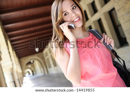 A pretty, young woman on the college campus talking on phone - stock photo