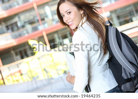 A pretty, young woman on the university campus walking to class - stock photo