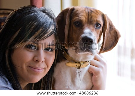 A pretty young woman posing with her beagle pup. Shallow depth of field. - stock photo