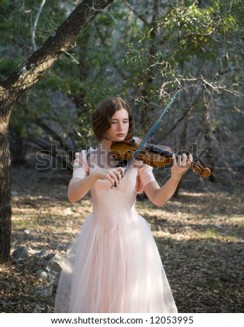 A pretty young woman/teenager in a vintage dress holding a violin and bow in a woodland setting.