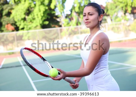 A pretty young woman tennis player getting ready to serve the ball - stock photo