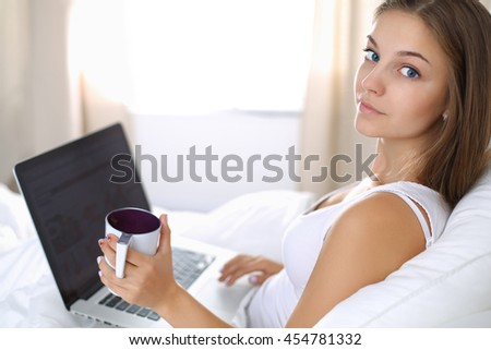 A pretty young woman with a laptop in bed and enjoying a cup of tea