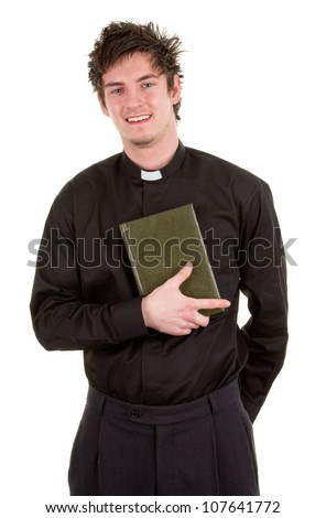 A priest isolated on white, holding a bible close to himself. - stock photo
