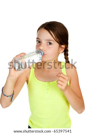 A primary aged girl drinking from a plastic bottle of mineral water. - stock photo